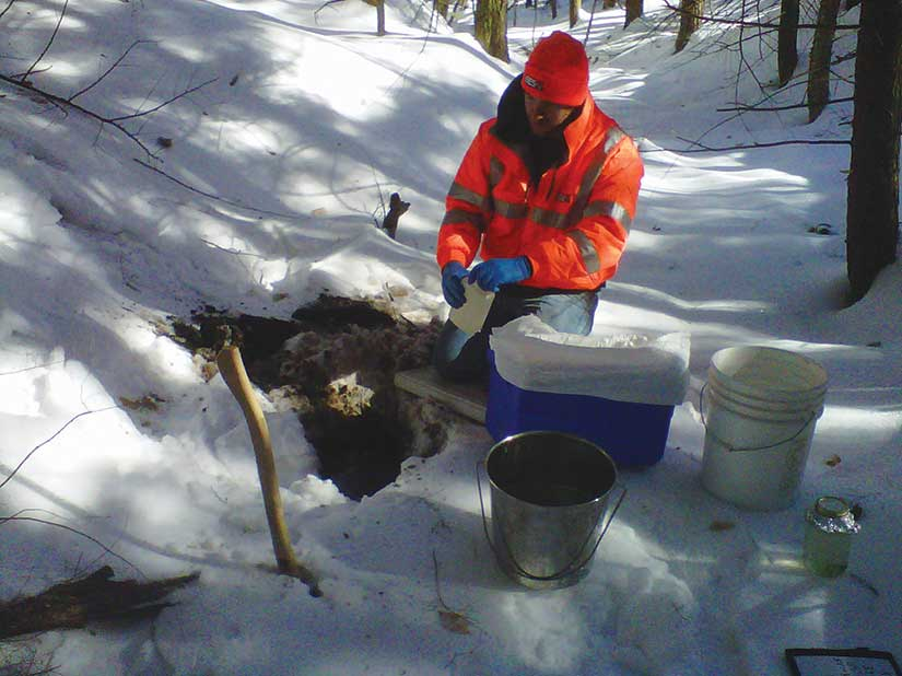 Man taking a dirt sample from a hold in the snow